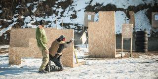 De instructeur onderwijst student tactisch kanon schietend achter dekking of barricade stock fotografie