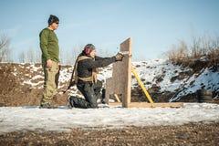 De instructeur onderwijst student tactisch kanon schietend achter dekking of barricade stock afbeelding