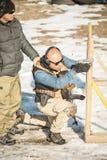 De instructeur onderwijst student tactisch kanon schietend achter dekking of barricade stock foto