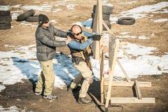 De instructeur onderwijst student tactisch kanon schietend achter dekking of barricade stock foto's