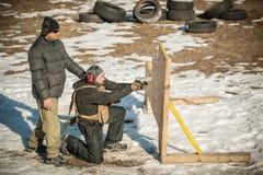 De instructeur onderwijst student tactisch kanon schietend achter dekking of barricade royalty-vrije stock fotografie