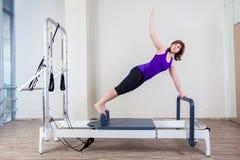 De instructeur van de gymnastiekvrouw pilate het uitrekken zich in hervormer stock foto's