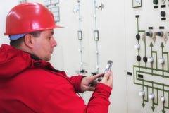 De instrumenten van de elektricienlezing en het verzenden sms in elektrische centrale Stock Afbeelding
