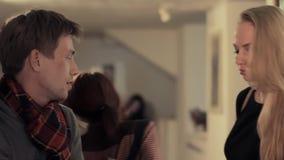 De intelligente kerel die aan aantrekkelijke vrouw bij kunstgalerie spreken, wordt onderbroken stock footage