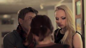 De intelligente mens die aan aantrekkelijk meisje over kunst in galerij spreken, wordt afgeleid stock video