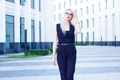 De intelligente vrouw loopt onderaan de straat tegen de achtergrond van het commerciële centrum royalty-vrije stock fotografie