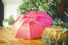 De intense kleur van de paraplu voegt vreugde aan de regen toe stock fotografie
