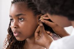 De Intern verpleegde patiënt` s Oor van artsenputting hearing aid stock foto