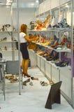 De internationale gespecialiseerde tentoonstelling voor schoeisel, zakken en toebehoren de vrouw van Mos Shoes kiest schoenen Royalty-vrije Stock Afbeeldingen