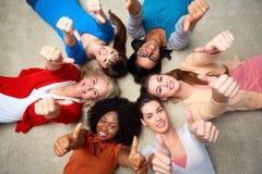 De internationale groep vrouwen het tonen beduimelt omhoog stock foto