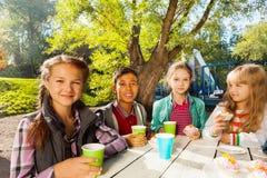 De internationale kinderen drinken thee buiten van koppen Royalty-vrije Stock Fotografie