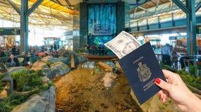 De Internationale Luchthaven van Vancouver - 11 April, 2017: Hand die een Canadees paspoort met een nota $5 houden in Vancouver I Stock Afbeeldingen