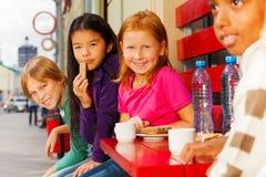De internationale vrienden die in koffie zitten en eten Stock Foto's