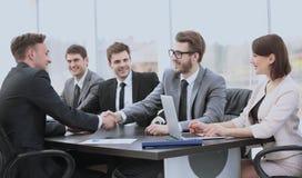 De investeerder schudt handen met de verkoopdirecteur om conclu te ondertekenen Stock Afbeelding