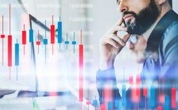 De investeerders die van de Cryprovoorraad voorzijde van bureaucomputer met technische prijsgrafiek en indicator, rood zitten en  stock foto