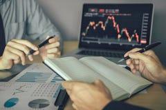 De investeerders gebruiken een pen aan het schrijven van gegevens voor het bedrijf dat de aandelen met collega's op het kantoor a royalty-vrije stock foto's