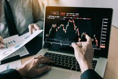 De investeerders richten aan laptops die de effectenbeurzen en hebben de partners die van de investeringsinformatie nota's en het stock afbeeldingen