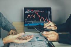 De investeerdersmens gebruikt digitale tabletten om informatie van bedrijf te vinden die effectenbeurs samen met collega's analys stock afbeelding