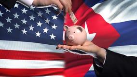 De investering van de V.S. in Cuba, hand die geld in piggybank op vlagachtergrond zetten stock videobeelden