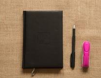 De inzameling van de bureaulevering - notitieboekjesnietmachine op bruine jute stock afbeelding