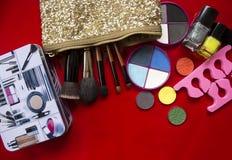 De Inzameling van de make-up Oogschaduw, make-upborstels op rood stock foto