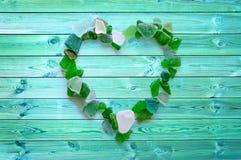 De inzameling van het strandglas in de vorm van een hart op blauwe planken royalty-vrije stock foto's