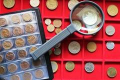 De inzameling van numismatische, wereldmuntstukken op een rood dienblad royalty-vrije stock afbeelding