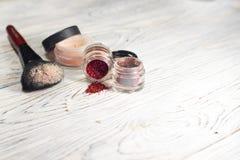 De inzameling van schoonheidsmiddelen voor grimeur Powder, pigment, schittert, borstels en eyeliner studiofoto op een houten acht Stock Foto's