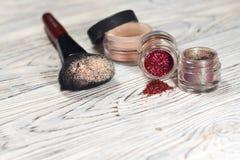 De inzameling van schoonheidsmiddelen voor grimeur Powder, pigment, schittert, borstels en eyeliner studiofoto op een houten acht Stock Foto
