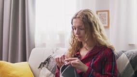De inzoomen van vrouwenzitting op bank en het breien haken kleren in comfortabel huis stock video
