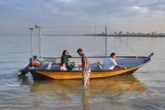 De Iraanse familie zit in motorboot op zonnige avond, Iran Stock Foto