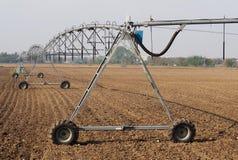 De irrigatiesysteem van de centrumspil op een geploegd gebied op een zonnige dag stock afbeeldingen
