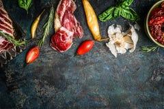 De Italiaanse antipastosnack met gerookt vlees, de tomaten en ciabatta paneren op rustieke achtergrond, hoogste mening royalty-vrije stock foto's