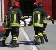 de Italiaanse brandbestrijders in actie dragen een brancard met verwonde af Stock Foto's