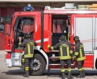 De Italiaanse brandbestrijders beklimmen op firetrucks tijdens een noodsituatie Stock Foto