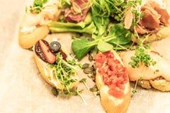 De Italiaanse die snacks van de antipastiwijn met Ondiepe diepte van nadruk over donkere grungeachtergrond worden geplaatst stock foto