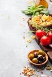 De Italiaanse voedselachtergrond met wijnstoktomaten, basilicum, spaghetti, olijveningrediënten op steen dient Exemplaarruimte in stock afbeelding