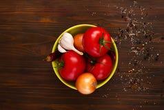 De Italiaanse voedselingrediënten, groenten in een groene kom op een houten achtergrond met kruiden, hoogste mening, exemplaar sp stock afbeelding