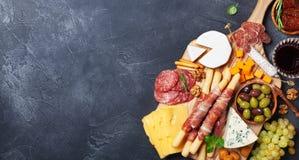 De Italiaanse voorgerechten of antipasto plaatsen met gastronomisch voedsel op zwarte de bovenkantmening van de steenlijst Gemeng royalty-vrije stock foto's