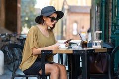 De Italiaanse vrouw met hoed en glazen schrijft bericht met smartphone stock foto