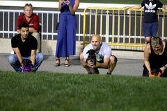 2de Jaarlijkse Worstjehond Derby Competitor dat door eigenaarwachten wordt gehouden om te beginnen stock afbeelding