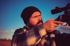 De jacht is de praktijk van het doden of het opsluiten van dieren Jager met jachtgeweerkanon op jacht stock fotografie