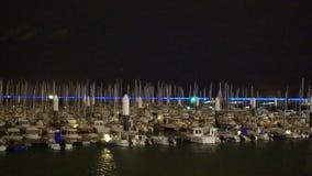 De jachten en de kleine boten legden bij jachthaven, nachtmening vast van schepen in grote haven stock video