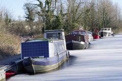 De jachthaven van de bootmeertros in de wintersneeuw en ijs bevroren water en houten pijlerpier bij aak varende club stock afbeelding