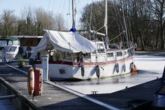 De jachthaven van de bootmeertros in de wintersneeuw en ijs bevroren water en houten pijlerpier bij aak varende club stock afbeeldingen
