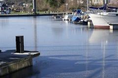 De jachthaven van de bootmeertros in de wintersneeuw en ijs bevroren water en houten pijlerpier bij aak varende club royalty-vrije stock afbeeldingen