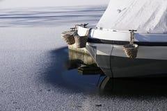 De jachthaven van de bootmeertros in de wintersneeuw en ijs bevroren water en houten pijlerpier bij aak varende club royalty-vrije stock foto's