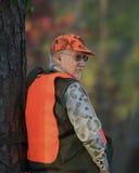 De Jager die van herten tegen Boom leunt Stock Foto's