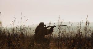 De jager in de jachtmateriaal ligt in wachttijd Het silhouet van de mens in zonsonderganglicht vindt het doel en het doel met gew stock video