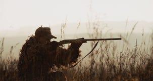 De jager in de jachtmateriaal ligt in wachttijd op het gebied Het silhouet van de mens in zonsonderganglicht vindt het doel en he stock videobeelden